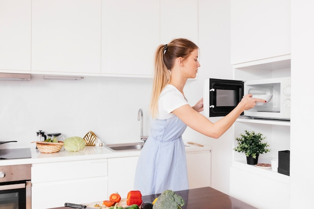Primer plano de mujer joven rubia insertando comida en horno de microondas