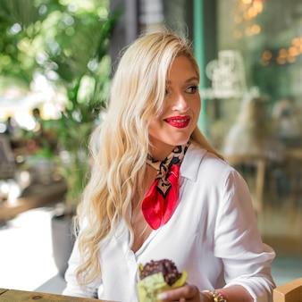 Primer plano de mujer joven rubia con muffin en la mano