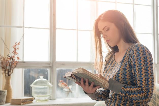 Primer plano de una mujer joven rubia de pie cerca de la ventana leyendo libro vintage