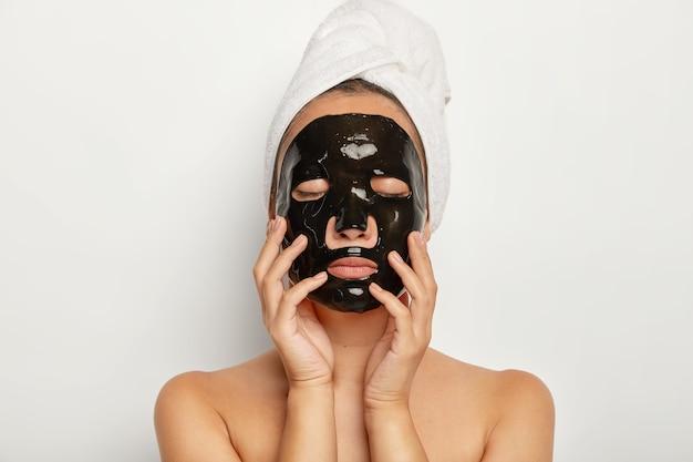 Primer plano de una mujer joven seria que usa una máscara facial negra, tiene los ojos cerrados, toca la cara suavemente, usa una toalla envuelta alrededor de la cabeza