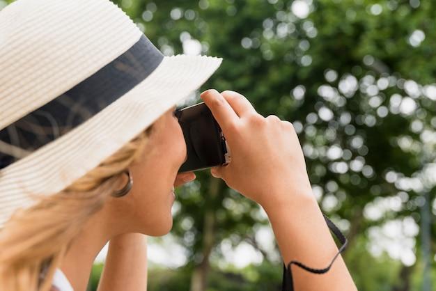 Primer plano de mujer joven con sombrero tomando fotografía de cámara