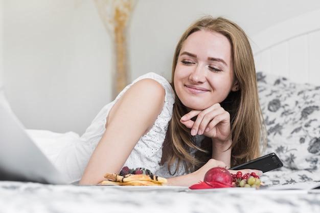 Primer plano de mujer joven sonriente acostado en cama con desayuno mirando portátil