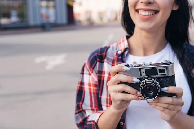 Primer plano de mujer joven sonriente con cámara retro al aire libre