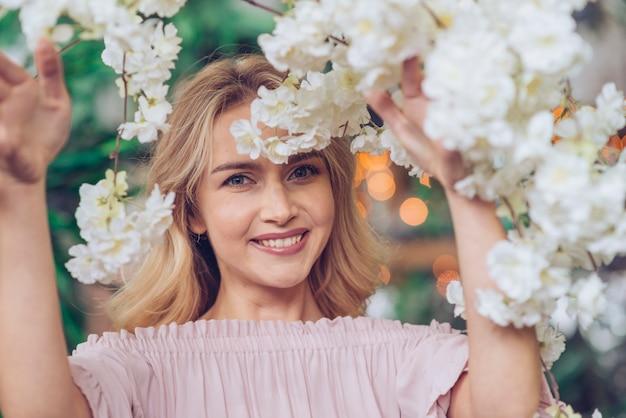 Primer plano de mujer joven sonriente mirando a través de flores blancas