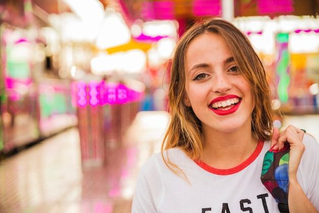 Primer plano de una mujer joven sonriente en el parque de atracciones