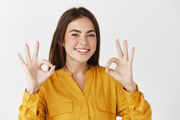 Primer plano de una mujer joven sonriente que le asegura, que muestra el signo bien y garantiza que todo es perfecto, de pie en la pared blanca