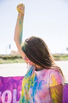 Primer plano de mujer joven sonriente rociando color holi sobre su cabeza