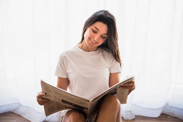 Primer plano de una mujer joven sonriente sentada frente a la cortina blanca leyendo el periódico