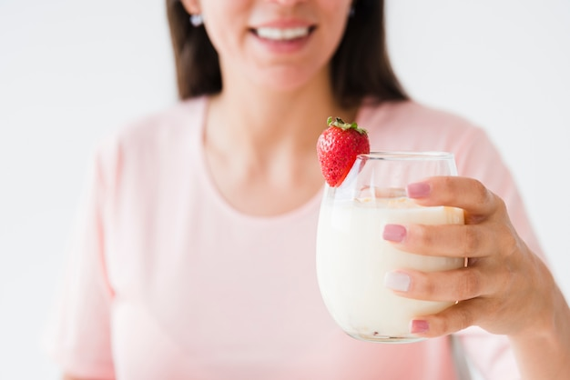 Primer plano de una mujer joven sonriente con vaso de yogur con fresa