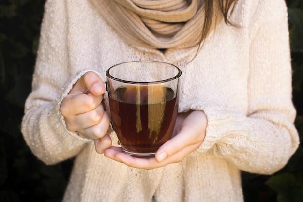 Primer plano de una mujer joven sosteniendo una taza transparente de té de hierbas