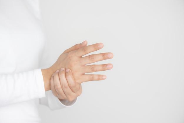 Primer plano de mujer joven sostiene su muñeca, lesión en la mano, siente dolor