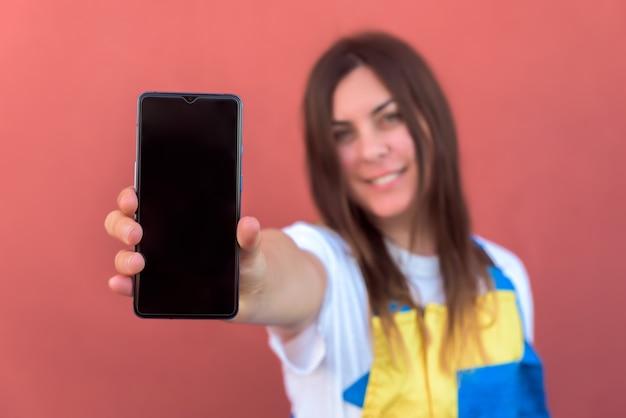 Primer plano de una mujer joven con su smartphone posando en la cámara