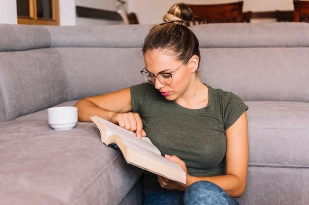 Primer plano de una mujer joven con una taza de café en el sofá leyendo el libro