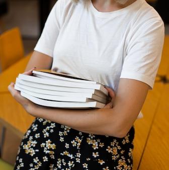 Primer plano, mujer joven, tenencia, libros