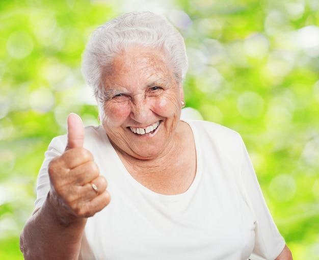 Primer plano de mujer jubilada con el pulgar hacia arriba