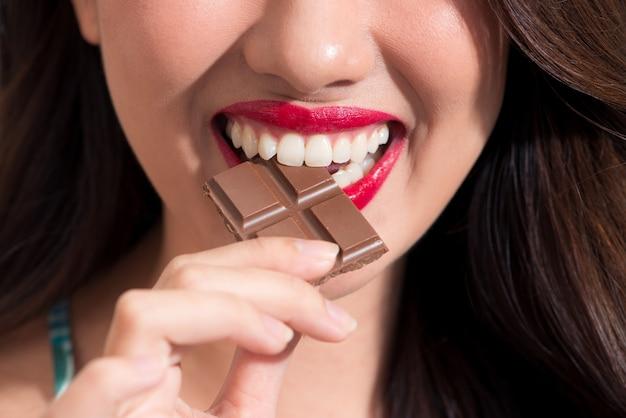 Primer plano de una mujer con lápiz labial rojo come chocolate