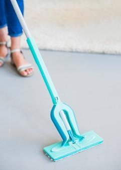 Primer plano de mujer limpiando el piso con fregona turquesa