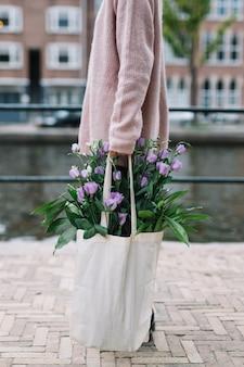 Primer plano de mujer llevando bolso con hermosas flores púrpuras de eustoma
