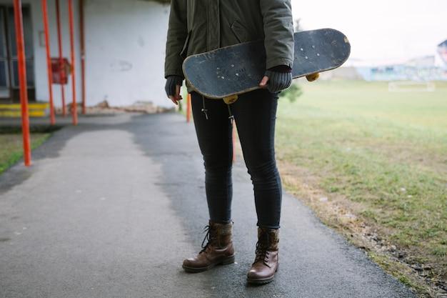 Primer plano de una mujer llevando patineta en mano