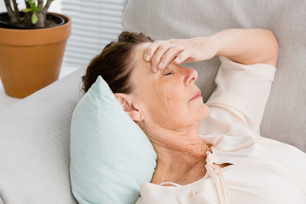Primer plano de mujer madura con dolor de cabeza mientras está acostado en el sofá