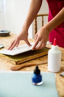 Primer plano, de, mujer, mano, colocar, cubierta, en, papel, pulpa, sobre, escritorio