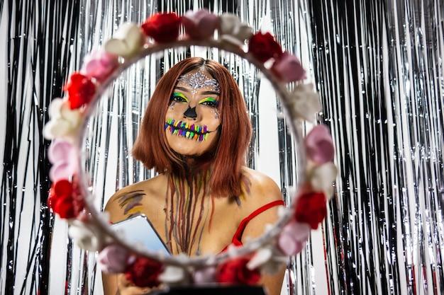 Primer plano de una mujer con maquillaje para halloween detrás de un círculo de flores y teléfono celular en la mano