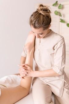 Primer plano, mujer, masajear, pierna