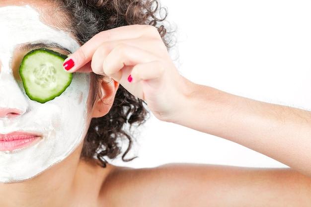 Primer plano de mujer con mascarilla nutritiva de limpieza profunda que sostiene pepino sobre los ojos
