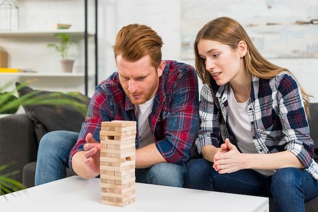Primer plano de mujer mirando al hombre arreglando el bloque de madera