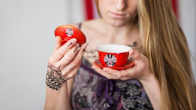 Primer plano de una mujer mirando el té tradicionalmente preparado en la taza