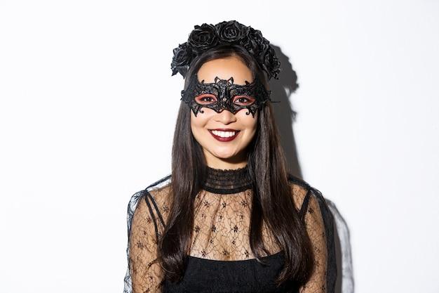 Primer plano de mujer misteriosa en corona gótica y máscara negra sonriendo a la cámara, celebrando halloween, de pie sobre fondo blanco.