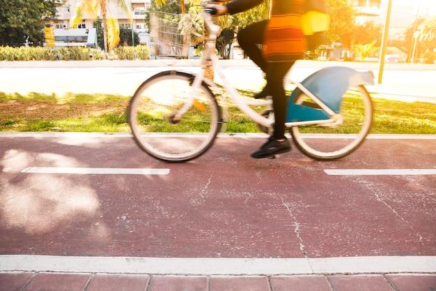 Primer plano de una mujer montando la bicicleta en el parque