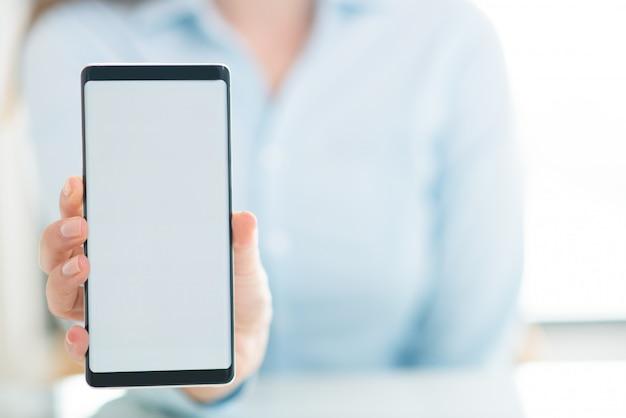 Primer plano de mujer mostrando la pantalla vacía del teléfono inteligente