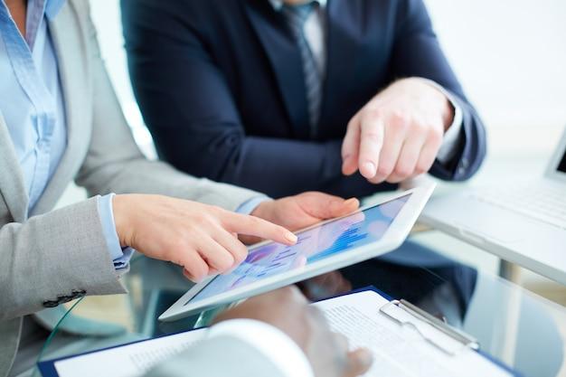Primer plano de mujer de negocios apuntando a la tableta digital
