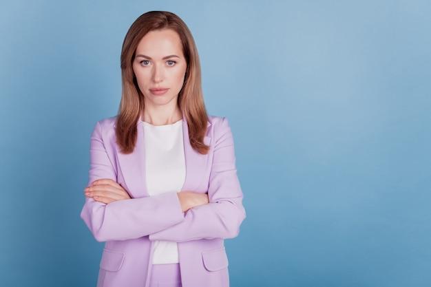 Primer plano de una mujer de negocios confiada mira la cámara con las manos cruzadas sobre fondo azul.