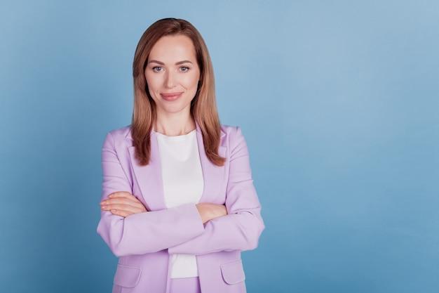 Primer plano de una mujer de negocios exitosa gerente mira la cámara con las manos juntas sobre fondo azul.