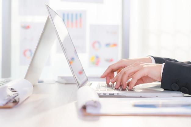 Primer plano de mujer de negocios de la mano escribiendo en el teclado del ordenador portátil