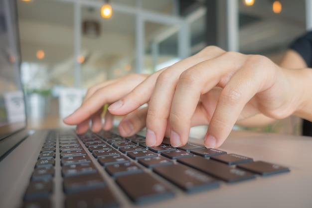 Primer plano de mujer de negocios de la mano escribiendo en el teclado del ordenador portátil.