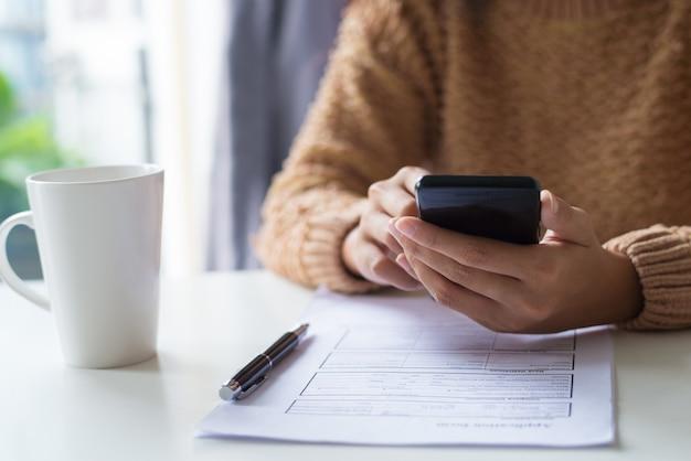 Primer plano de una mujer de negocios que usa un aparato mientras examina un documento