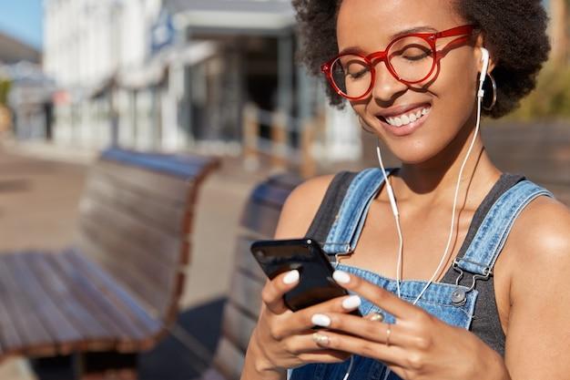 Primer plano de la mujer negra sonriente meloman disfruta de la radio en línea, sostiene el teléfono móvil, está conectado a auriculares digitales, usa gafas ópticas, modelos contra la calle al aire libre borrosa