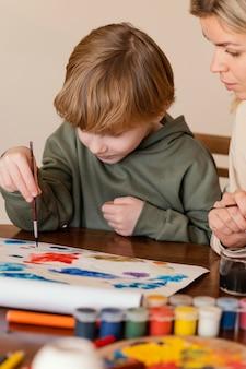 Primer plano mujer y niño pintando sobre papel