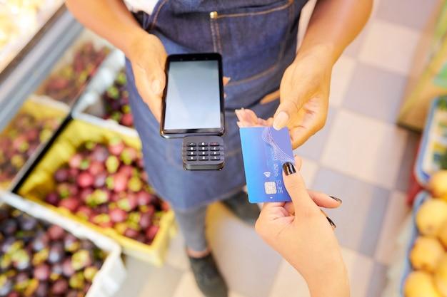 Primer plano de mujer pagando su compra con tarjeta de crédito mientras el vendedor sostiene el terminal en la tienda