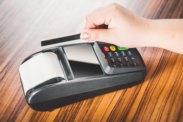 Primer plano de mujer pasando su tarjeta de crédito