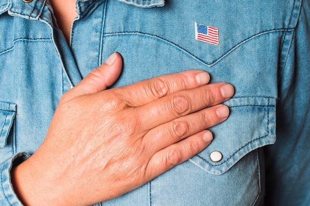 Primer plano de una mujer patriótica con la mano en el corazón
