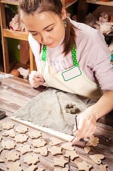 Un primer plano de una mujer de pelo oscuro alfarero hace juguetes de año nuevo de arcilla chamuscada utilizando moldes de metal corazones, asteriscos, peces pequeños