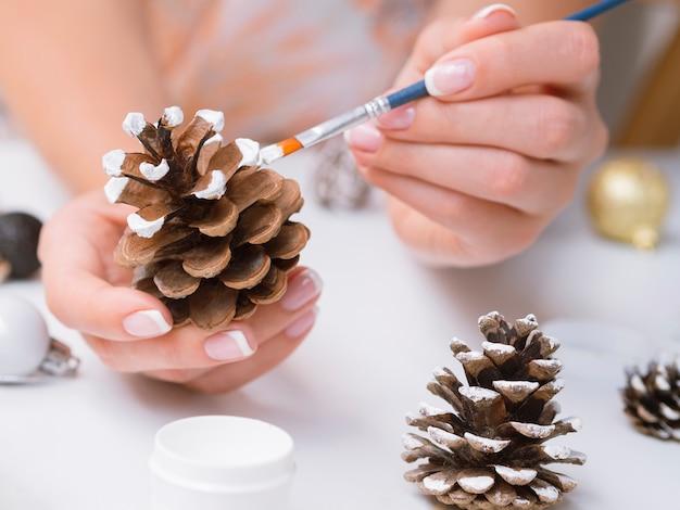Primer plano de mujer pintando conos de pino