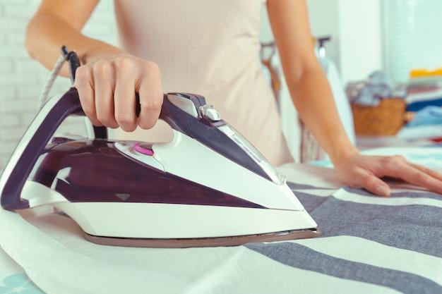 Primer plano de mujer planchando ropa en tabla de planchar