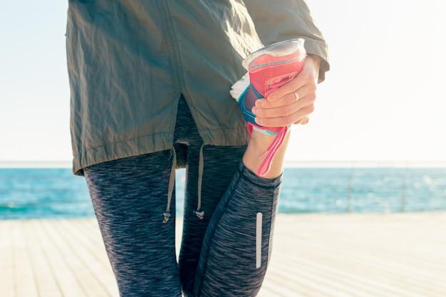 El primer plano de la mujer en la playa estira los músculos de la pierna