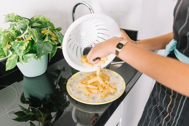 Primer plano de mujer poniendo pasta en el plato