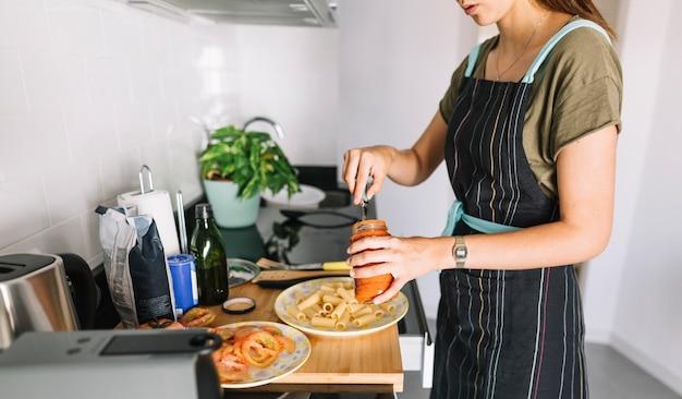 Primer plano de mujer poniendo salsa en la pasta cocida en el plato